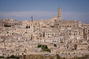 The modern city buildings can be seen atop a hill with the many layers of ancient cave dwellings beneath it in Matera, Italy.