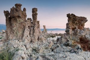A landscape photograph of vertical tufa formations at Mono Lake rise in front of a pink and blue sunrise sky
