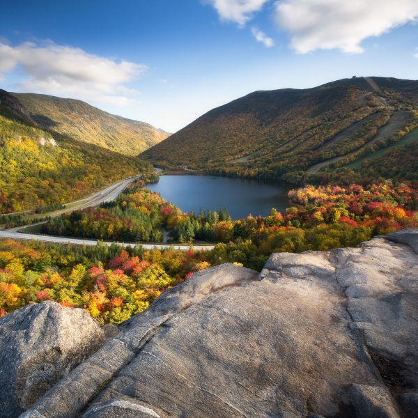 Looking out over a rocky cliff to see franconia notch filled with orange, red and yellow trees surrounding a lake and the ski trails of Cannon Mountain