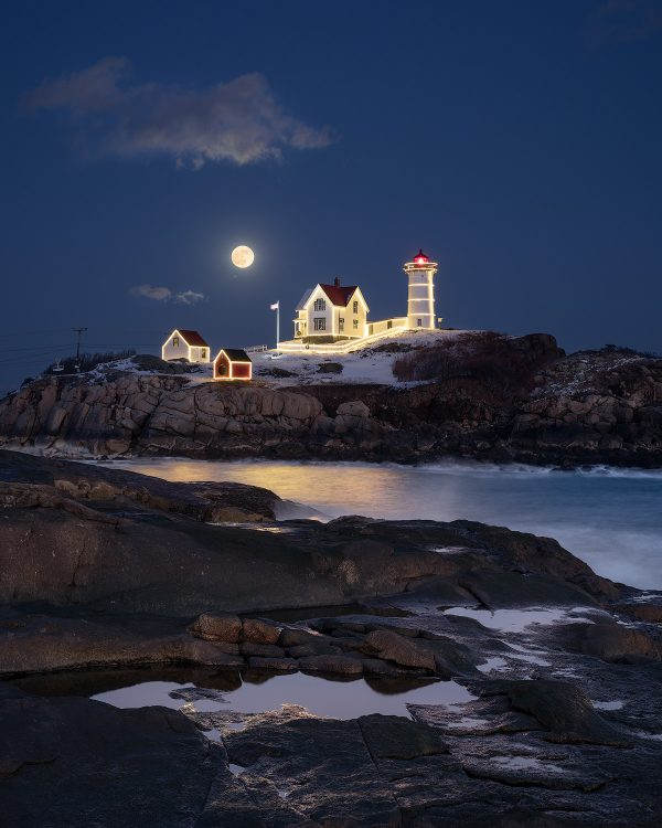 A full moon rises over a snowy nubble lighthouse with christmas lights in york beach maine