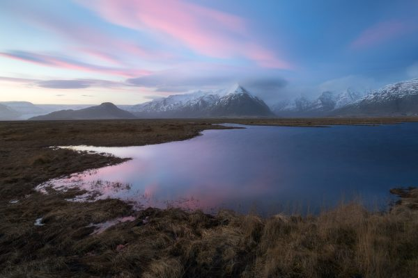 An alpine pond reflects the sunset sky with snow capped mountains off in the distance.