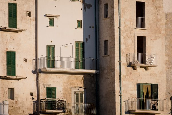 A travel photograph of green doors and windows on the clifftop houses in Polignano a Mare in Puglia, italy.