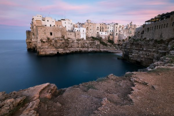 A long exposure photograph of the centro storico clifftop buildings in Polignano a Mare in Puglia Italy taken by female landscape photographer Kathryn Wallace Yeaton