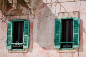 A travel photograph of a peach colored building and two windows with mint green colored shutters in Polignano a Mare Italy.