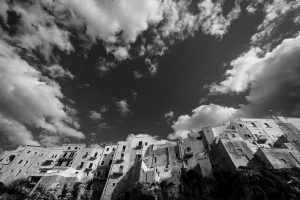A black and white image of the clifftop buildings of Polignano a Mare and a cloudy sky in puglia, Italy.