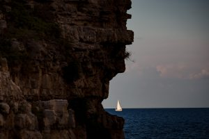 A white sailboat peeks out from behind a cliff in Puglia, Italy.