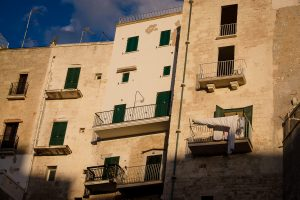 The sun-drenched clifftop buildings of Polignano a Mare in Puglia, Italy.