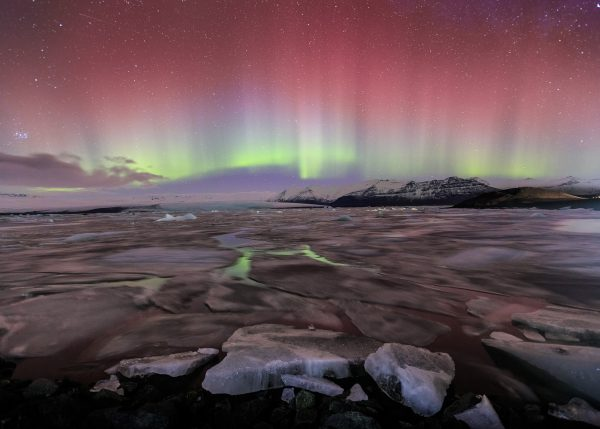 The sky glows red and green with aurora borealis above the Jokulsarlon glacier lagoon in Iceland