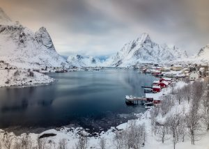 Snow capped mountains stand behind the red fishing shacks and sea inlet of Reine in the Lofoten Islands of Norway.