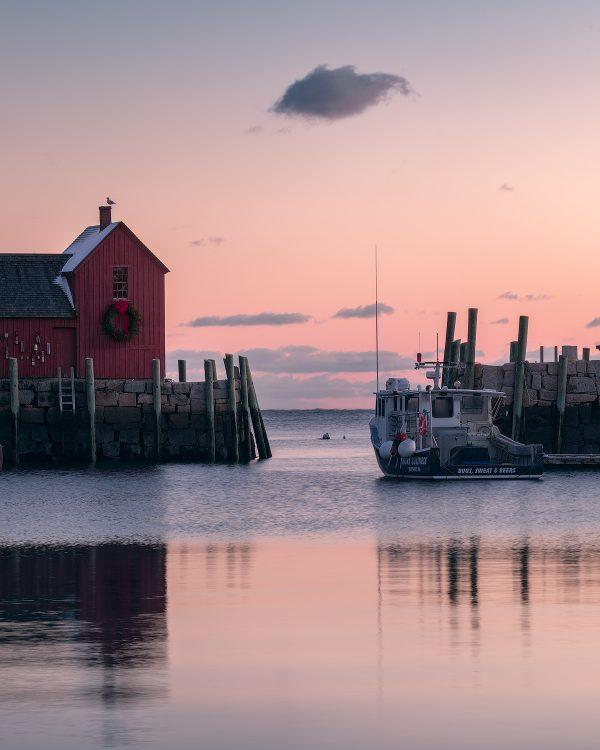 A pink winter sunrise behind the red fishing shak and boats of rockport harbor massachusetts