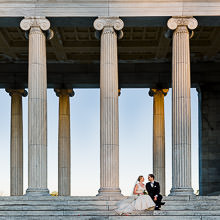 A bride and groom sit on the steps of the Roger Williams Park Temple to Music in Providence, RI