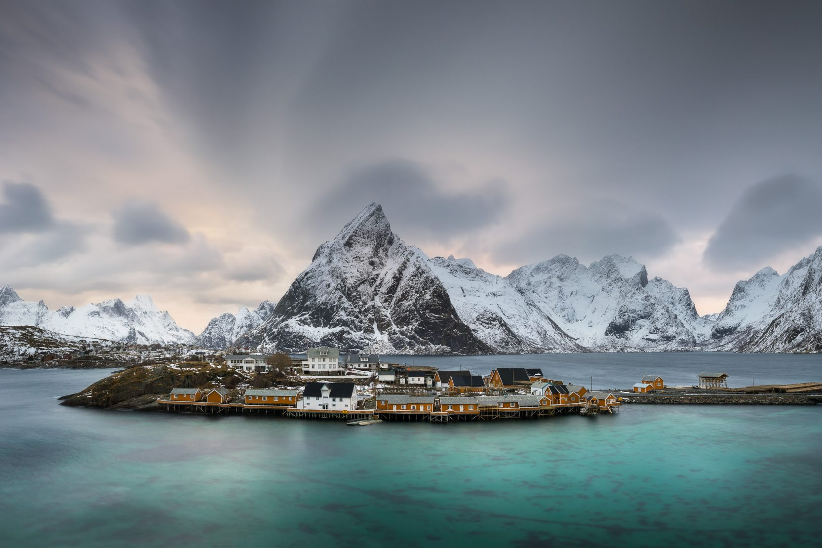 Jagged snow capped mountains rise behind the turquoise sea and picturesque fishing village of Sakrisoy in the Lofoten Islands of Norway