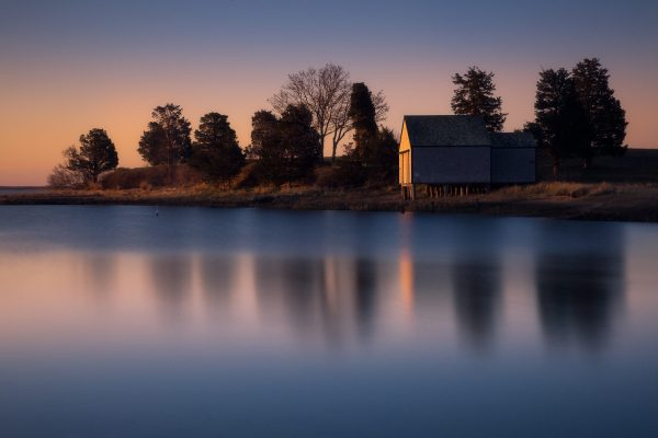 A sunrise sky glows orange behind a boathouse that is reflecting in the salt pond in Eastham Cape Cod.