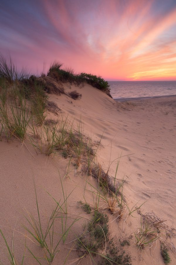 An s-shaped dune reached up to a fiery sunset sky in Wellfleet, Cape Cod