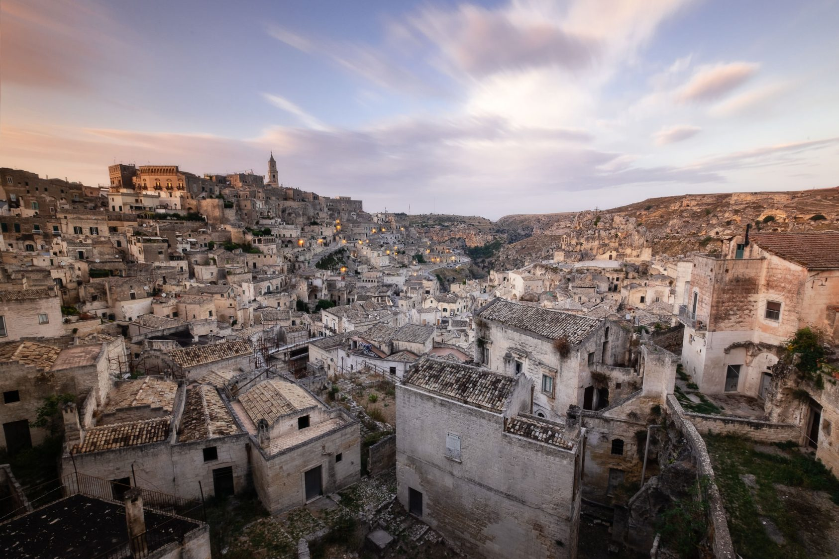 The ancient houses in the Sassi di Matera with a sunset ski overhead in Matera, Italy.