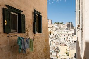 Laundry hangs on the side of a stone building with the ancient city of Matera, Italy in the distance.