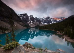 The snowy 10 peaks mountains glow red with sunrise light and are reflected in a glassy blue moraine lake in banff alberta canada.