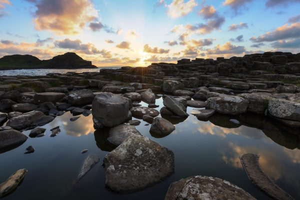 A small pool of water reflects the clouds and sky amidst many hexagonal towers at Giant's Causeway in Northern Ireland.