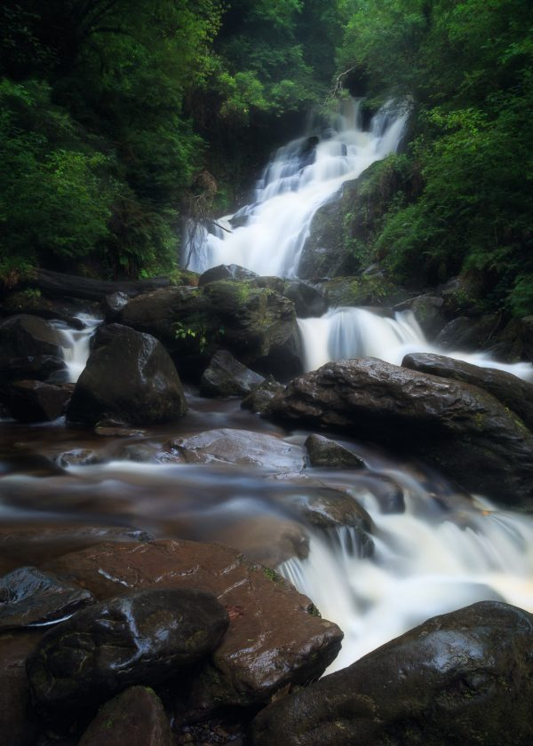 Torc waterfall cascades through misty green trees and red rocks in Killarney National Park Ireland.