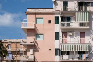 A travel photograph in pastel hues of aqua and peach of an apartment building in Viesta Puglia Italy.