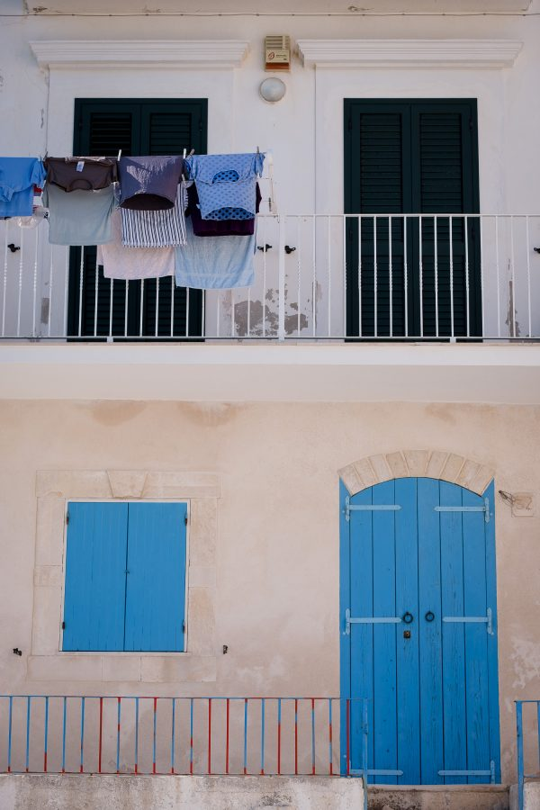 A travel photograph of a bright blue door and hanging laundry in shades of blue in Vieste, Italy.
