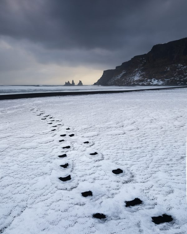 A set of black sand footprints extend through the snow to the sea stacks at Vik Iceland.