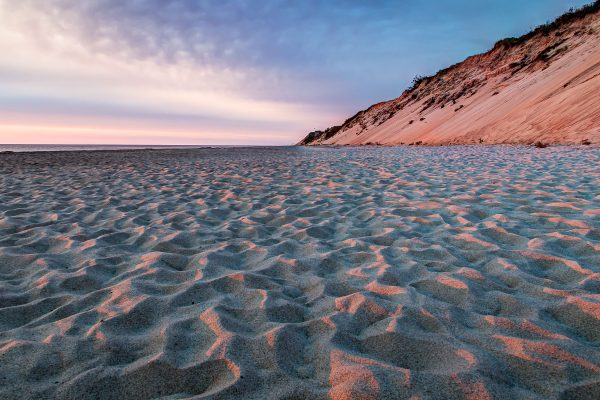 The rising sun casts orange light on sand ripples and a large sand dune on a beach in Wellfleet, MA