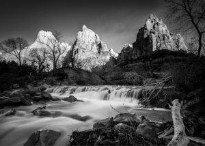 A black and white photograph of a river flowing below stone monoliths in Zion National Park