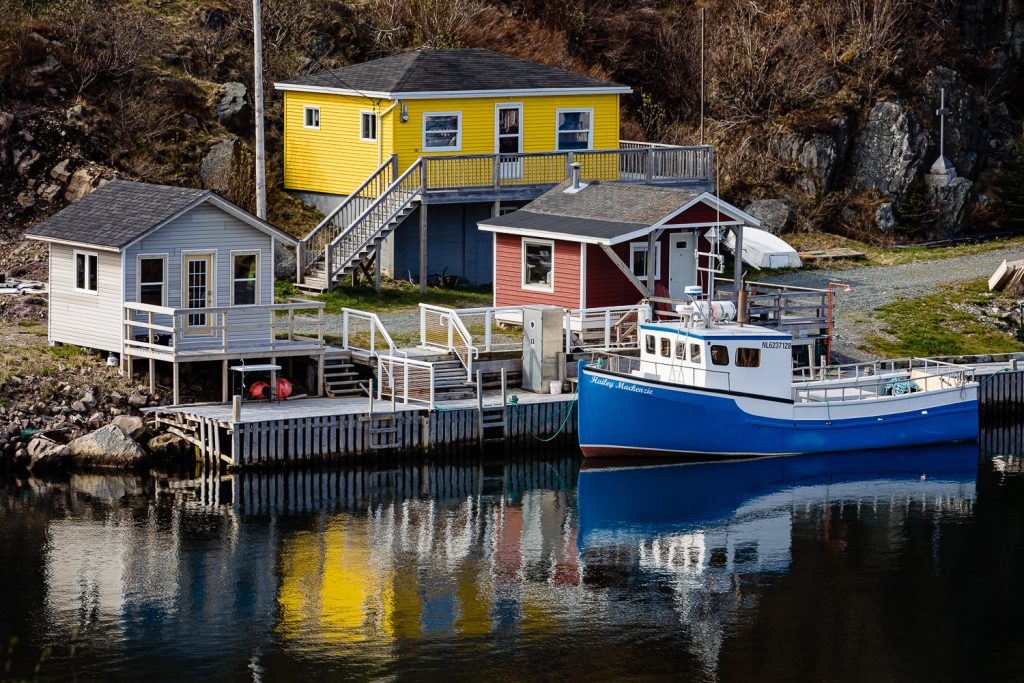 A photo of primary color fishing shacks and boat in the quidi vidi battery in St. John's Newfoundland