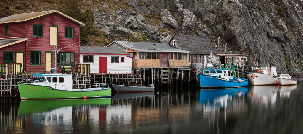 A panorama photo of fishing shacks and boats in Quidi Vidi neighborhood of St. John's newfoundland.